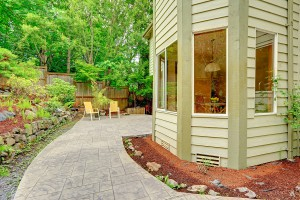 Walkout patio with sitting area and backyard leveled landscape design with stones. Tile walkway